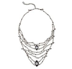 Short necklace made up of various leather strands of rounded silver-plated beads and two rhombus-shaped, grey Swarovski crystals.