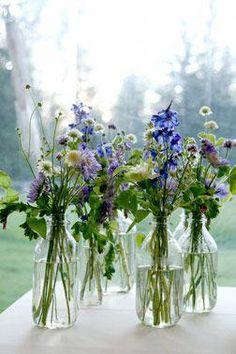 wild flowers in large bottles #weddingtableflowerarrangementsgreen