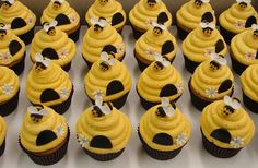 Bumble Bee Beehive Cupcakes. These adorable cupcakes feature two flavors, Snickerdoodle with vanilla buttercream frosting and pumpkin with vanilla buttercream frosting. The buttercream is tinted to a warm yellow and piped to resemble a beehive. Each cupcake is highlighted with a fondant hive opening, flower and a classic bumblebee tops it off. Browse our full dessert gallery at www.jmccustomcakes.com .