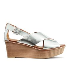 Platform sandals in imitation leather with a metallic finish. Wedge heels, ankle strap with metal buckle, imitation leather lining and insoles, and rubber soles. Front platform height 1 1/4 in., heel height 2 3/4 in.