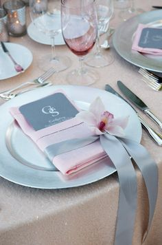 A fabulous setting with single pink orchid and gray sash.