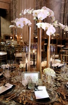 A glitzy glamorous Great Gatsby inspired tall wedding centerpiece with gold eiffel tower vases and cascading orchids. Event design and planning by Modern Day Events and Floral. Photography by Karyn May Photography....