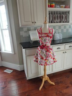 Our cute Ooh La La - Annie Style Work Apron - Red Floral in Designer Riley Blake Fabric - Beautiful Quality - fabric with pretty ric rac trim - - This is a cute but functional apron. It loops over the neck and ties at the waist in the back. Waist tie can wrap around to tie in front as