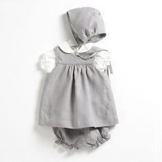 Conjunto compuesto por un vestido con cubrepañales y capota a juego en tonos gris claros y una blusa de manga corta y cuello de bebé blanca.
