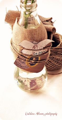 Up-cycle glass bottle into a unique vase. Wrap with burlap, twine, and vintage labels.