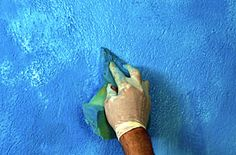Painting walls using the decorative ragging technique.