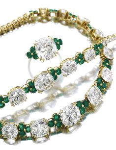 ATTRACTIVE DIAMOND AND EMERALD PARURE, ALEXANDRE REZA Comprising: a necklace set to the front with fifteen cushion-shaped diamonds interspersed with clusters of circular-cut emeralds, to a line of brilliant cut diamonds, length approximately 375mm, numbered, French assay and maker's mark; and a bracelet and ring en suite, bracelet length approximately 175mm, ring size 521/2, each signed A. Reza and numbered, French assay and maker's marks.