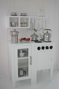 Simple and elegant play kitchen. Reminds me of Julia Child; needs pea green peg board with tool/pot outlines!
