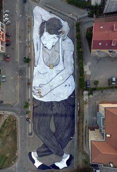 Campania, la street art si ammira dall'alto: c'è un gigante che dorme sull'asfalto
