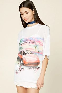 """A semi-sheer woven top featuring graphics including """"La Jolla"""", """"San Diego"""",a sports car, palm trees, and sky graphics on the front, a ribbed neckline, short sleeves, and an oversized silhouette."""