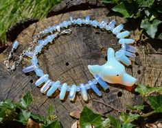 Magnificent Witch Queen necklace featuring a large carved Opalite wolf's head, Opalite icicles and beads, crystals and seed beads.Opalite (also known as Sea Opal or opalised glass) is a man-made gemstone known for it's striking appearance - it flu.