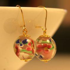 Vaaleanpunaisista lamppuhelmistä tehdyt korvakorut, joissa kullanväriset, nikkelittömät koukut ja koristeosat.