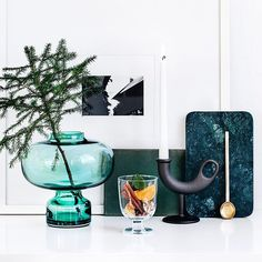 the Alfredo vase by Georg Jensen, Lempi glass by Iittala, Ildhane candleholder by Nedre Foss Gård, Gustav plate by Louise Roe Copenhagen and brass spoon by Ferm Living.