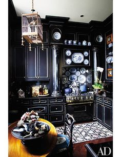 Designer Friederike Kemp Biggs, a passionate collector of antique porcelain, displays an array of blue-and-white pieces in the kitchen of her New York penthouse. The cabinets are painted with a rubbed finish of black over Chinese blue and limned in gold.