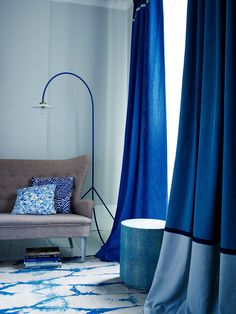 An eye catching curtain in a deep, vivid blue, adds impact in an otherwise neutrally decorated room. Smart asymmetrcial banding at the top and bottom of the floor to ceiling drapes has a strong modern look. Homes & Gardens, Curtain Call, Finishing Touches, March 2014, Photography Jake Curtis, Styling Lorraine Dawkins