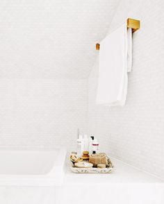 White tiled bathroom organized with a tray.