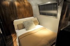 """Overlander-007. This is a renovated 1967 Overlander Airstream camper designed by Architect Series. It's been completely overhauled and redesigned from top to bottom! Bill Sheppard, the designer, says, """"we knew we had something good when it sold in less than 20 minutes of being listed!"""" When you go inside you'll see a cozy couch, fireplace, kitchenette, dining area, bedroom, and bathroom along with wood floors, modern fixtures, and more. Please enjoy, learn more, and re-share below."""