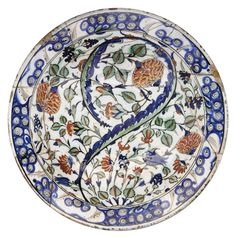 A LARGE IZNIK POTTERY DISH OTTOMAN TURKISH, EARLY 17TH CENTURY With sloping rim and rounded cavetto on short flat foot, the gilt and painted decoration with a long curled saz leaf among roses, hyacinths and tulips, the foot drilled