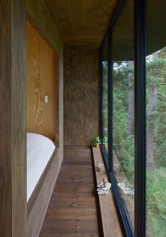 This bedroom in a summer house has views of the garden outside through large floor-to-ceiling windows.