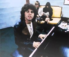 Jim Morrison messes around on piano during the filming of The Doors' movie, 'Feast of Friends'.