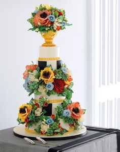 A five-tiered yellow #cake filled with chocolate mousse and vanilla and caramel buttercreams, iced with buttercream and decorated with hand-molded sugar flowers, from Sylvia Weinstock Cakes, sylviaweinstock.com