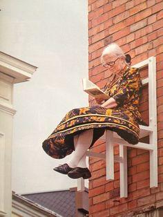 X-mal Mensch Stuhl von der deutschen Künstlerin und Performerin Angie Hiesl. Ältere Menschen auf weißem Stühle, die auf Gebäuden montiert sind sitzen  7 4  Kunst Jane Platman
