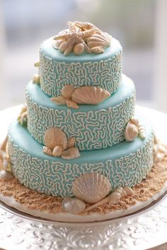 Intricately patterned icing in pale turquoise and white pops against cream-colored shells.    Source