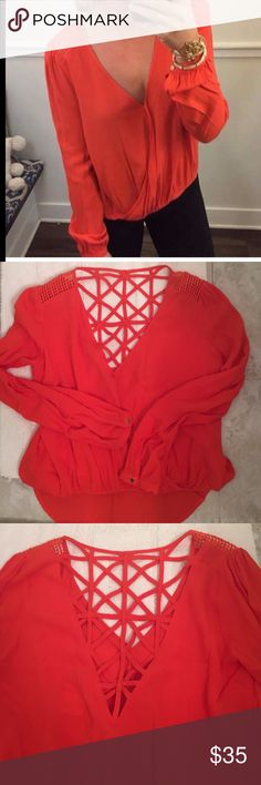 Red/orange strappy back long sleeve blouse Red blouse with crochet cut out shoulders. And a lattice cross cross back. Button detail on long sleeves. High low hem. Size medium. NWT. Bought it and it was too big for me. From apricot lane boutique.  Label brand is Onetheland. apricot lane boutique Tops Blouses
