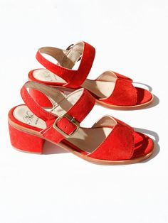 Wear-all-day block heel sandal in brilliant red suede. Adjustable ankle strap. Double-needle stitching. Heavy outer welt. Elastic at brass buckle for flexibility. Camel leather lining and insole. Sued