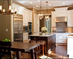 White kitchen cabinets with dark wood island.