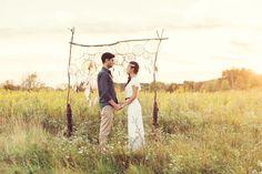 Simply Elegant Group Bohemian Prairie Wedding Inspiration. Boho ceremony backdrop, vows, exchange, background, arch, archway, dreamcatchers, feathers, DIY, doilies, vintage, prairie, field
