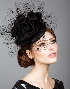Straw pillbox with straw rose and veiling.