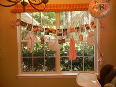 Pictures, clothes pins, newborn clothes and yarn to make an easy first birthday party decoration!