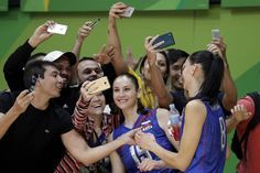 Russia's Tatiana Kosheleva, center and Nataliya Goncharova meet with fans after a women's preliminary volleyball match against…