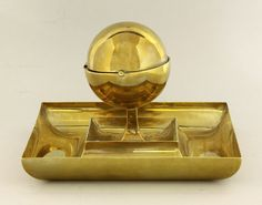 A Wiener Werkstatte brass inkwell, by Josef Hoffmann (1870-1956), the spherical inkwell with revolving lid on a square dished base, stamped 'Made in Austria, Wiener Werkstatte and JH' monogram Sold for £3200 29th July 2014