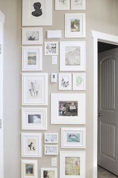 Strakke fotowand met witte lijsten. Ondanks dat er bij deze fotowand allerlei verschillende lijsten zijn gebruikt, blijft het beeld rustig. Dit komt door het strakke vlak waarbinnen alle lijsten zijn opgehangen en doordat er voor 1 kleur lijsten (wit) is gekozen.