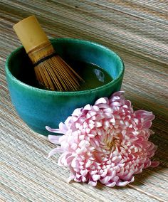 Japanese tea bowl and bamboo whisk, with delicate pink chrysanthemum flower.