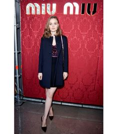 @Who What Wear - Bella Heathcote                 Wearing: Miu Miu black tricotine coat, bordeaux embossed velvet cap-sleeve dress, pink waistband, natté wool skirt, two-tone pink shoulder bag, and burgundy suede pumps.