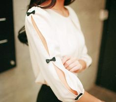 White slit-sleeved blouse with black bowtie fasteners