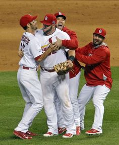 Matt Carpenter, Tony Cruz and Daniel Descalso surround Matt Adams, the hero of the game, as the team starts to celebrate after the last out of Game 4 of the NLDS between the Cardinals and the Dodgers. Photo by J.B. Forbes, jforbes@post-dispatch.com