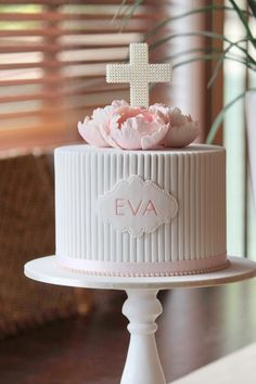 A beautiful cake with a pearl encrusted crucifix by Couture Cupcakes