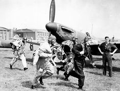 Spitfire pilots rush to their cockpits in RAF Duxford Battle of Britain 1940.