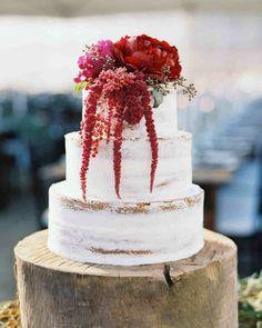 gâteau de mariage d'automne sur tronc-d'arbre avec fleurs rouges