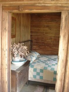 Log cabin bedroom. Blue and white quilt.