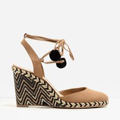 Covered brown wedge sandals featuring a weave detail espadrille design. Ankle strap fastens with a pom-pom lace-up closure.