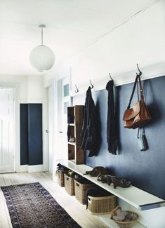 Navy blue and white entryway mudroom with a white pendant light, vintage Persian runner and baskets under the bench for extra stylish storage.