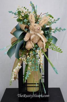 Our lantern swags are great way dress up any lantern! This swag is made with natural burlap ribbon, emerald ribbon, various flowers, plush bunny,