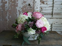mounds of hydrangea and peonies in a porcelain serving bowl