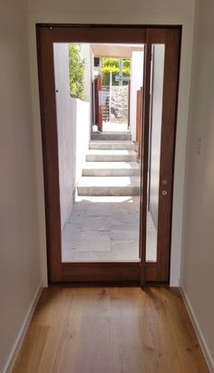 Single light timber front entry pivot door with full-sized timber handle
