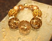 This bracelet has Beige, Yellow, Gold beads and gold accented beads.  This bracelet is strung on stretch string.